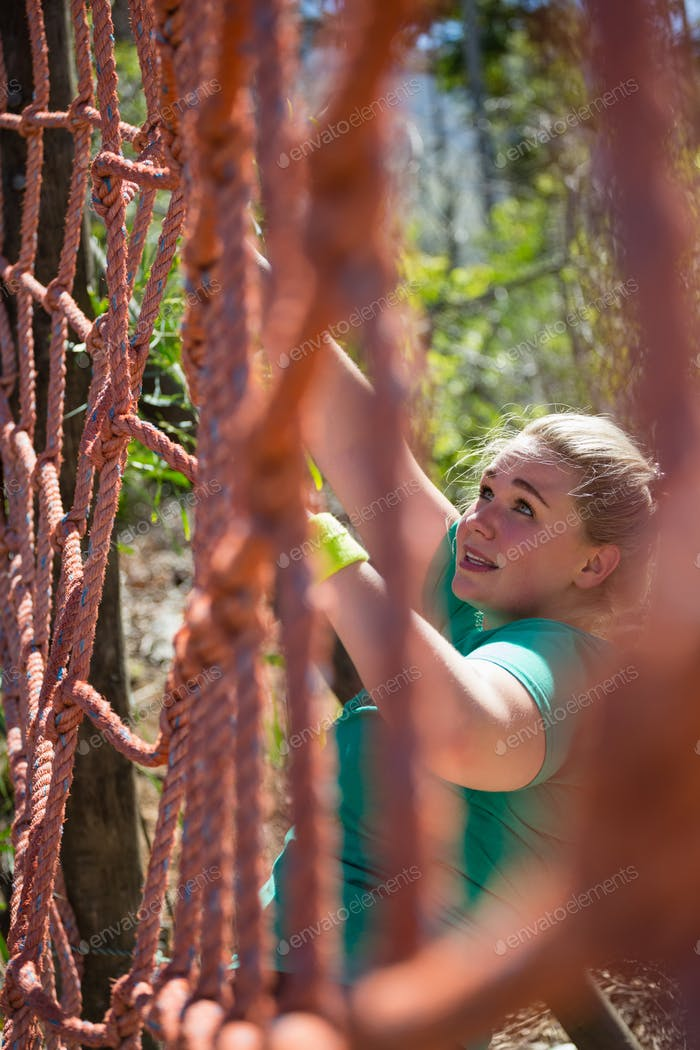 Determined woman climbing a net during obstacle course training