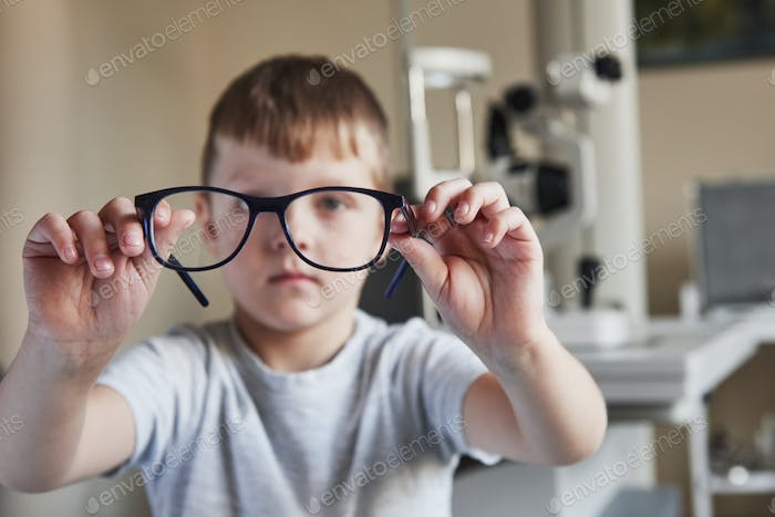 Boy holds the glasses on his elongated hands with ophthalmological equipment in the background