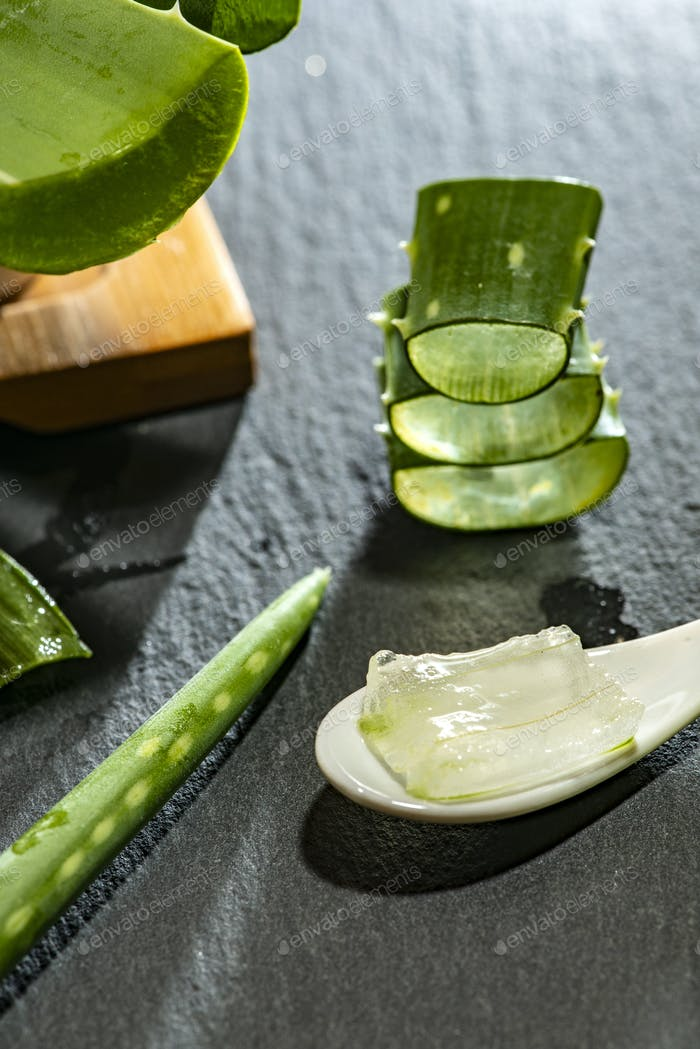 Aloe vera slices on dark background and spoon with aloe gel. Hea