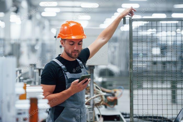 Smartphone in hand. Industrial worker indoors in factory. Young technician with orange hard hat