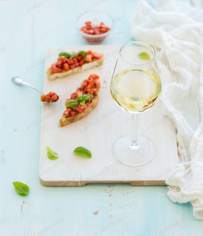 Glass of white wine, tomato and basil bruschetta sandwich