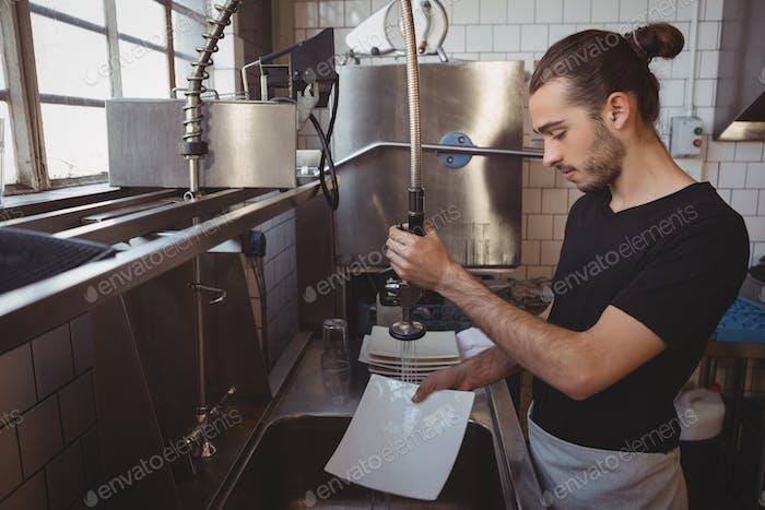 Waiter washing plates in cafe