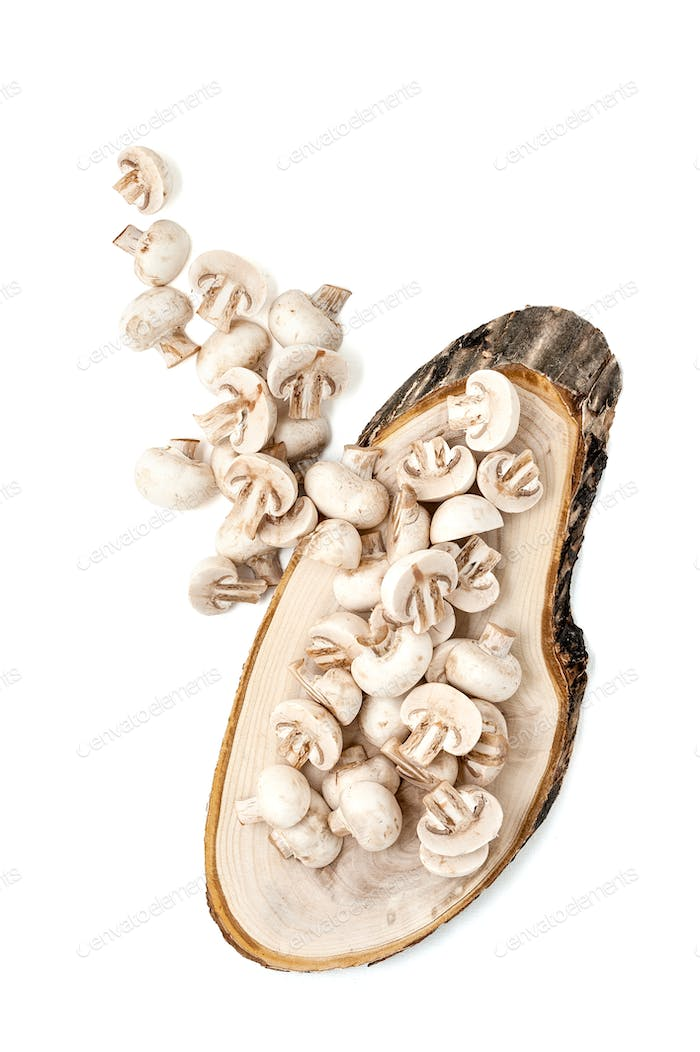 Cut mini champignons on a wood log. Isolated over white backgrou