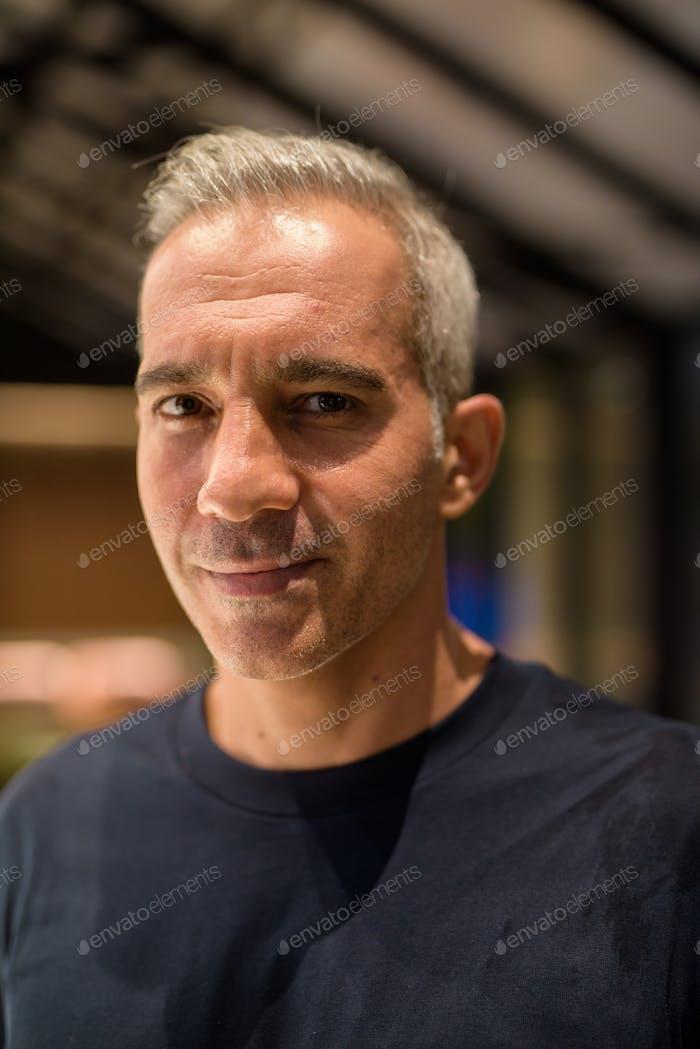 Portrait of man inside coffee shop at night