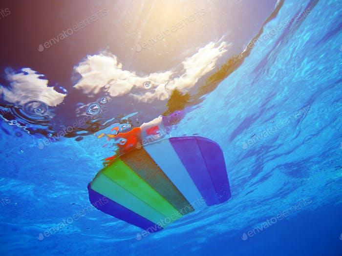 Rainbow pattern styrofoam swimming board floating in poolside wa