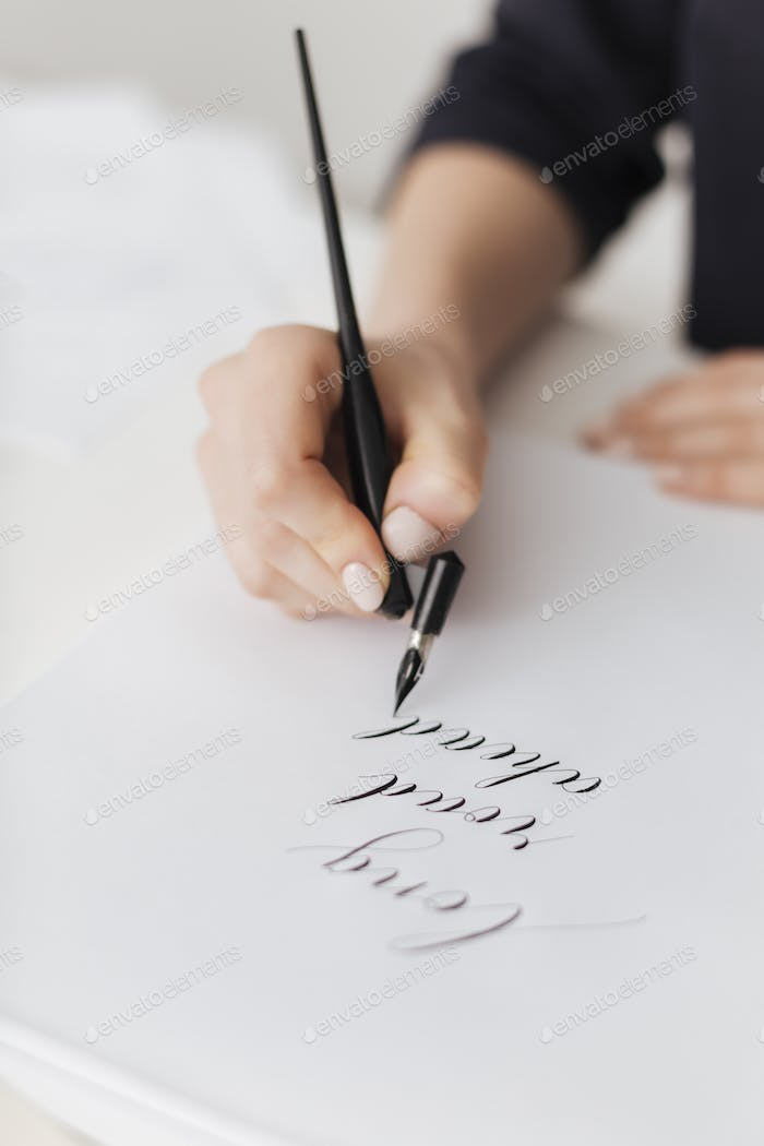 Close up photo of woman hands holding classic ink pen and writing beautiful postcard isolated