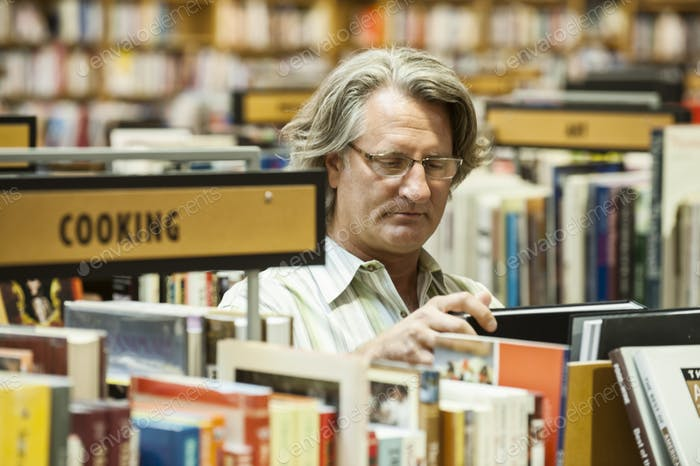 Caucasian male browsing through books in a large bookstore.