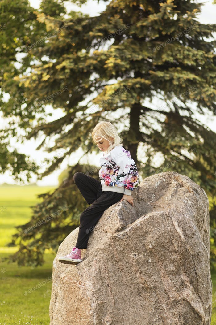 Girl sitting on rock at field