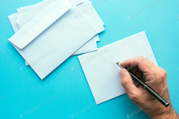 Hand writing address on blank white envelope