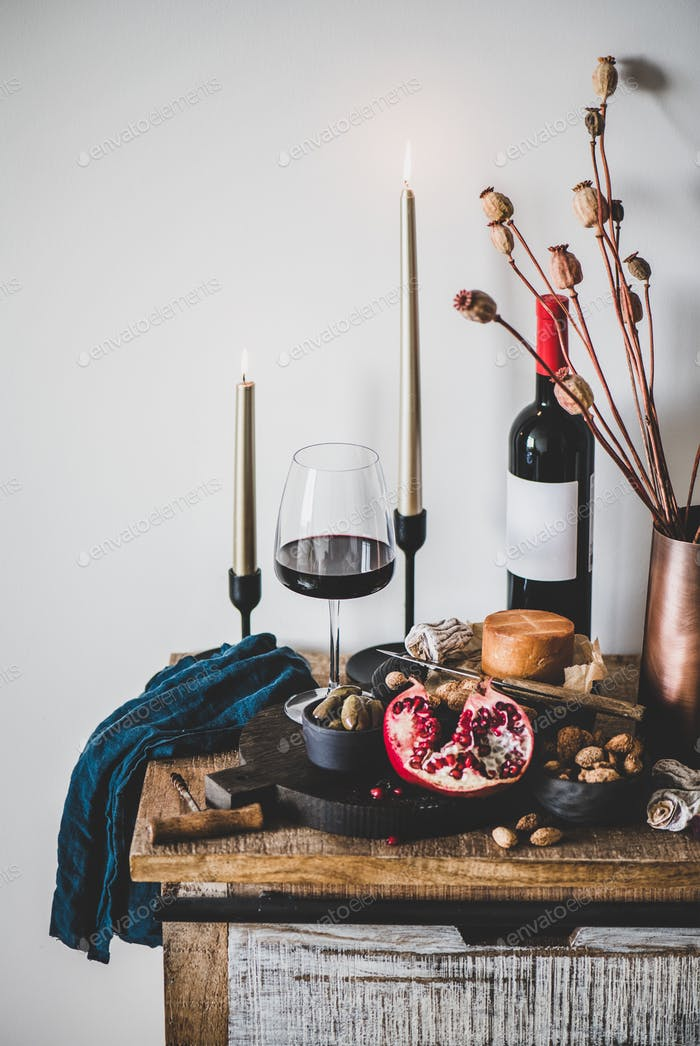 Red wine and appetizers over rustic wooden kitchen counter