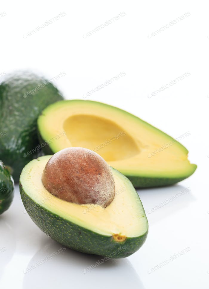 Healthy lifestyle concept. Avocados whole and half on white background.