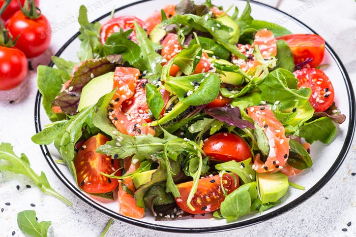 Salmon salad with fresh vegetables on white