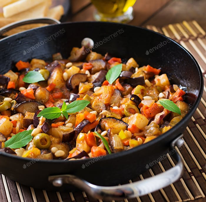 Italian Caponata with frying pan on a wooden background