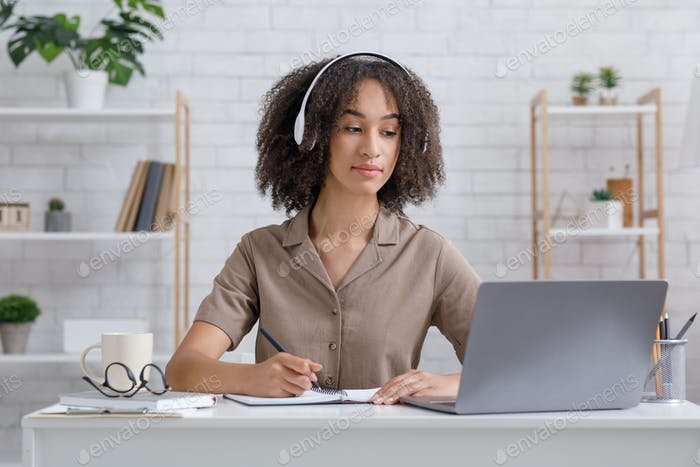 African american millennial student in headphones sit at desk, watch webinar and making notes
