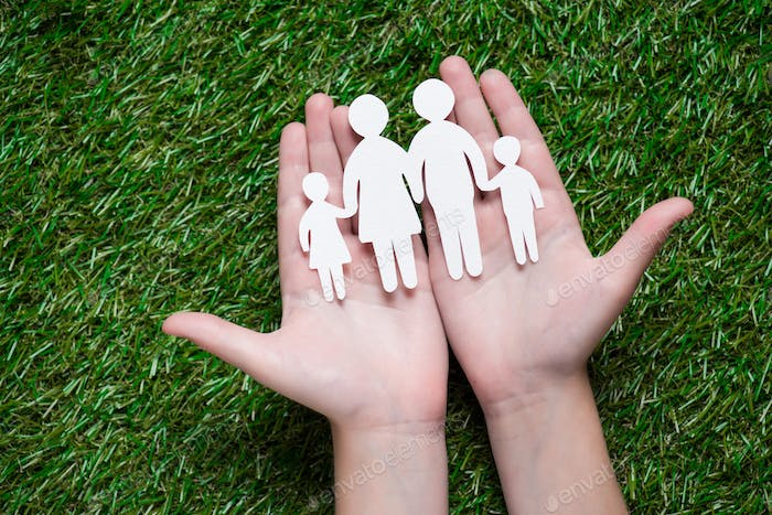 human hands holding paper cut of family on grass