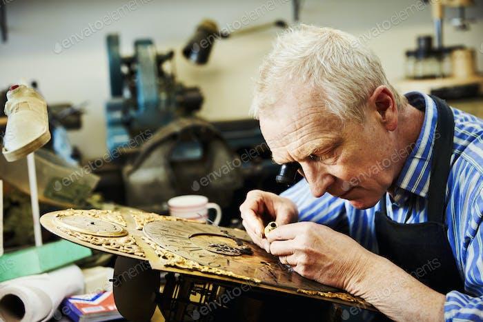 A clock maker using an eye loupe, working on an antique clock.