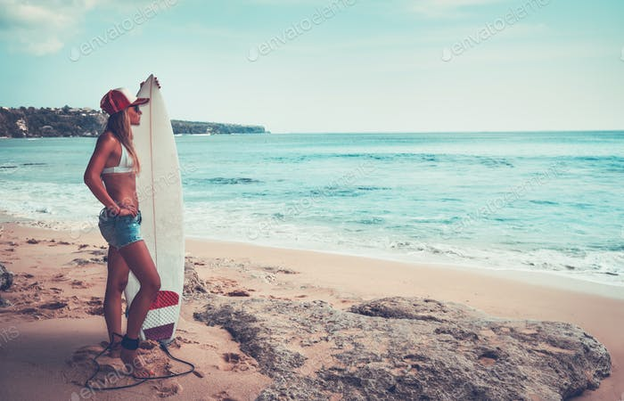 Beautiful surfer girl on the beach