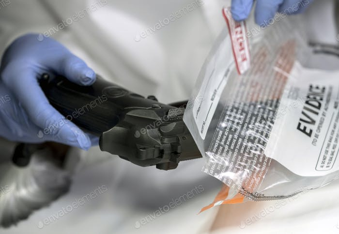 Scientific police officer examining traces of a gun in ballistic laboratory