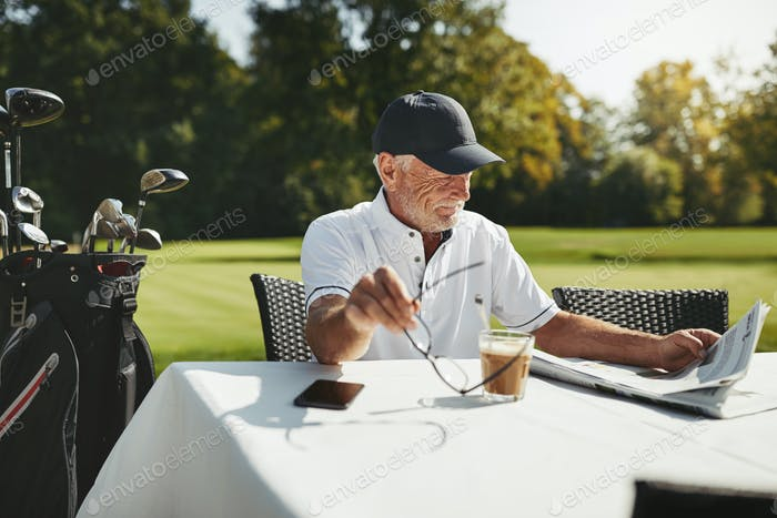 Senior man sitting at a cafe after playing golf