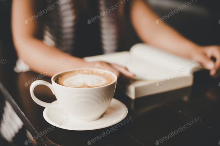 Asian woman relaxing and reading a book in the cafe. Women lifestyle concept.