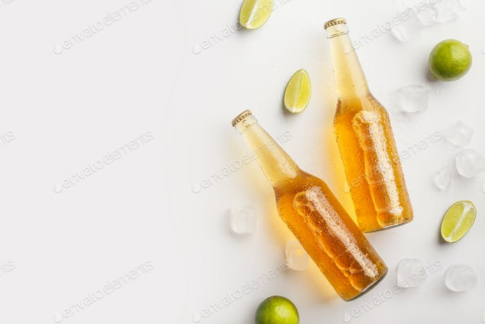 Freshen up and drink at summer. Bottles with beer in ice and pieces of lime on white background