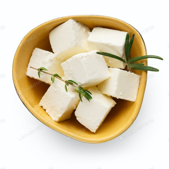 Feta cheese cubes in bowl on white