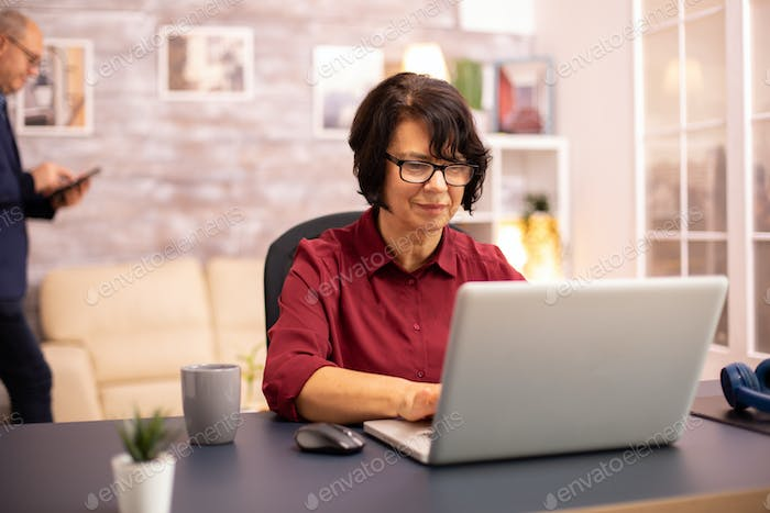 Old woman in her 60s using a modern laptop in her cozy house