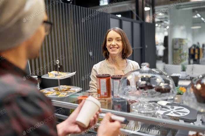 woman and man or barman with coffee cup at cafe