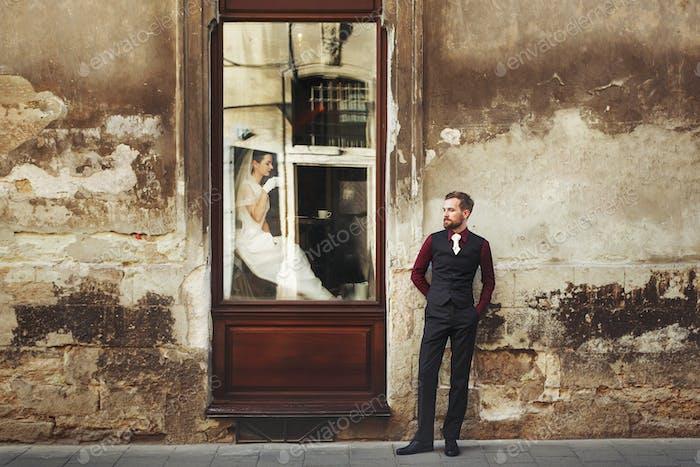 Невеста пьет кофе в окне и стильный жених позирует у здания