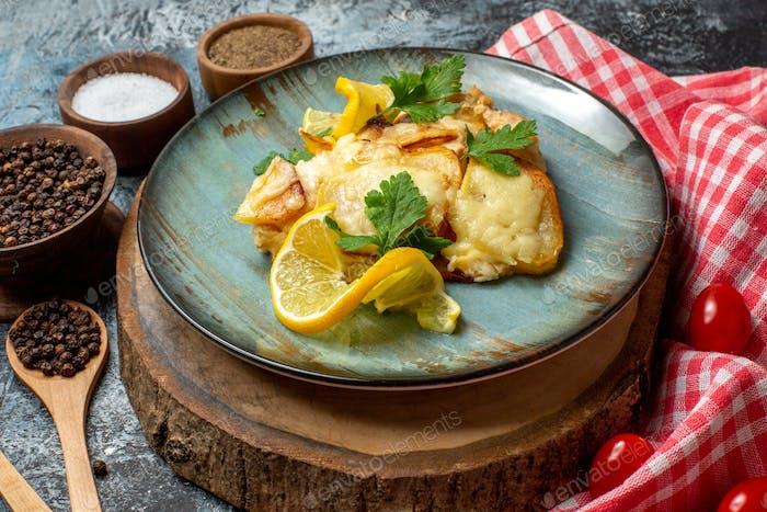 Ansicht von unten leckerer gebratener Fisch mit Zitrone und Petersilie auf Teller auf Holzbrett Petersiliengewürzschüsseln