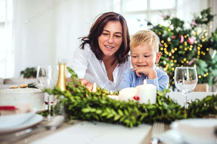 A small boy with grandmother sitting at the table at home at Christmas time.