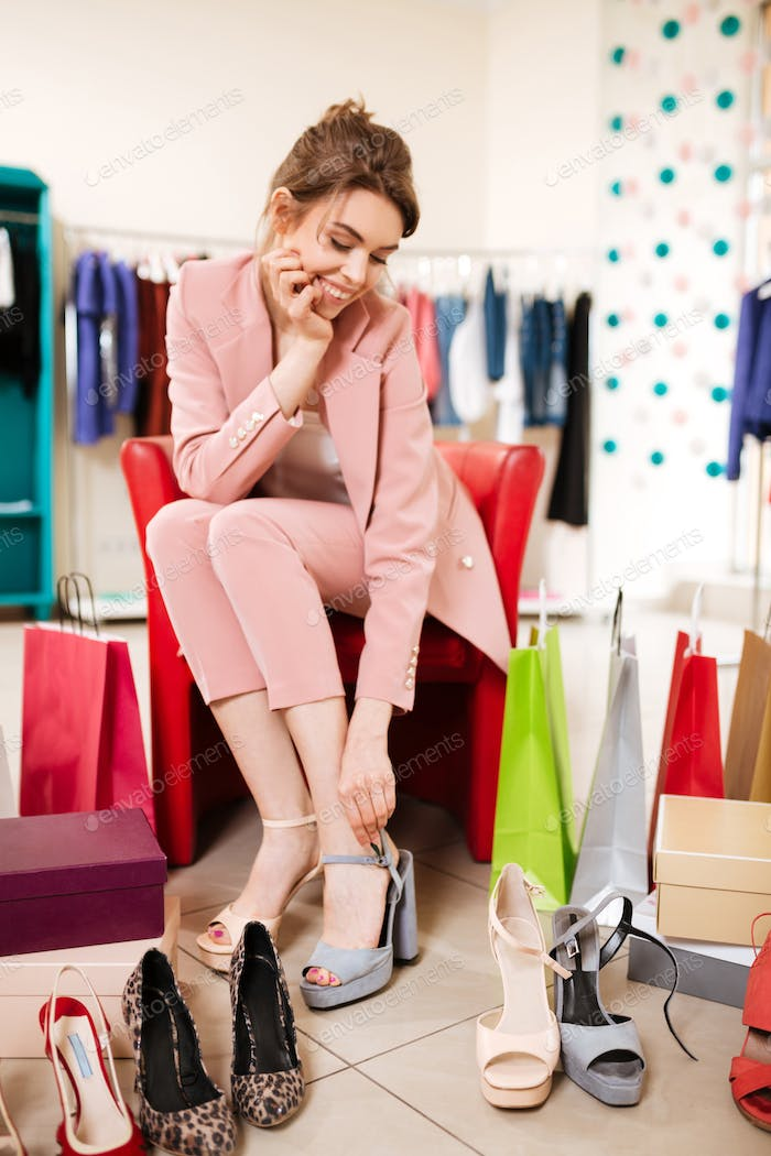 Girl with brown hair in pink pantsuit sitting on chair and thoughtfully measuring shoes at store