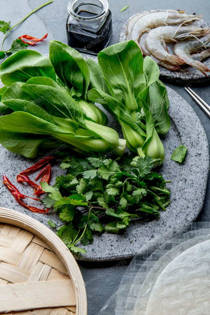 Asian cooking ingredients: rice papper, pok choy, sauces, raw shrimps.