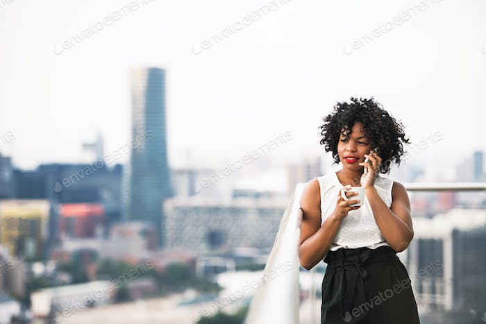 A businesswoman standing against London view panorama, making a phone call.
