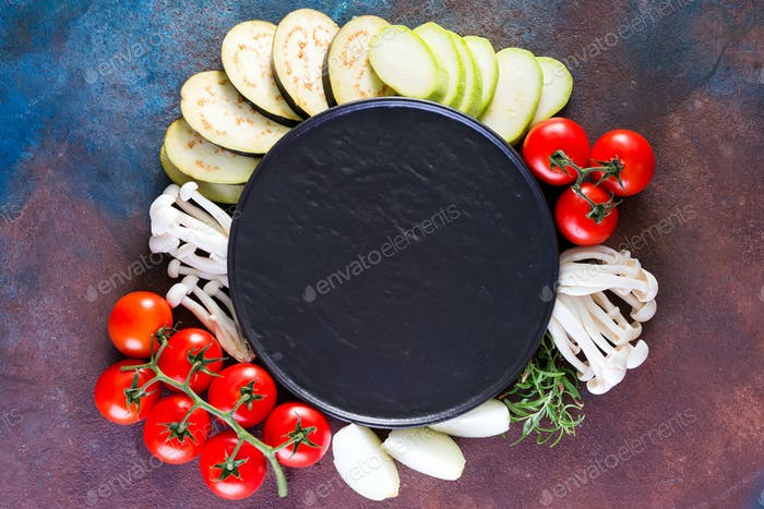 Top view of fresh vegetables for tasty cooking or salad making around empty stone plate on rustic