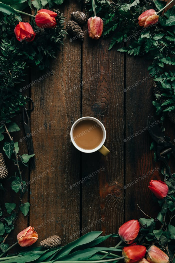Coffee cup on wooden table with tulips and various leaves.