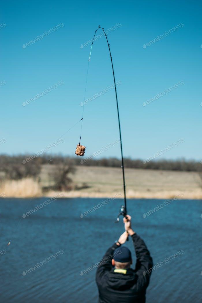 Feeder fishing. Carp Fishing Steel Basket Bait Feeder on rod close up. Male fisherman fishing at sun