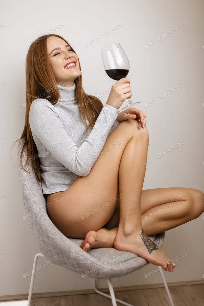 Beautiful smiling lady sitting in chair with glass of red wine in hand on gray background