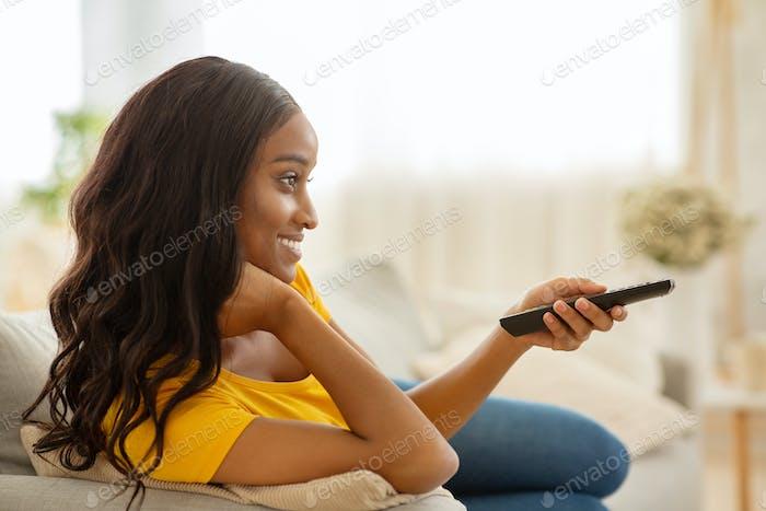 Оставайтесь дома развлечений. Улыбающаяся черная женщина с пультом дистанционного управления смотреть телевизор на диване в гостиной