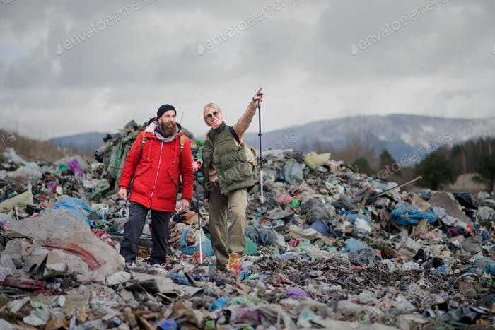 Man and woman hikers on landfill, environmental concept