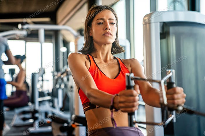 Attractive young sporty woman is working out in gym