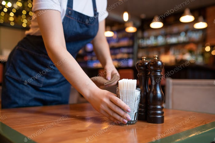 Young waitress in apron putting glass with toothpicks on wooden table