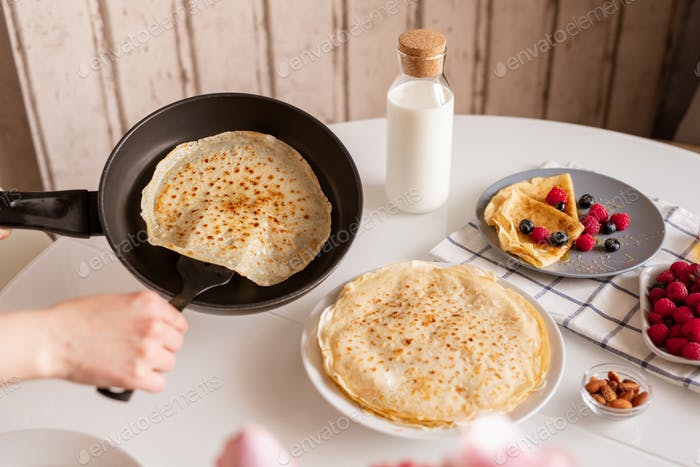 Hand of young female with frying pan taking hot appetizing pancake while cooking