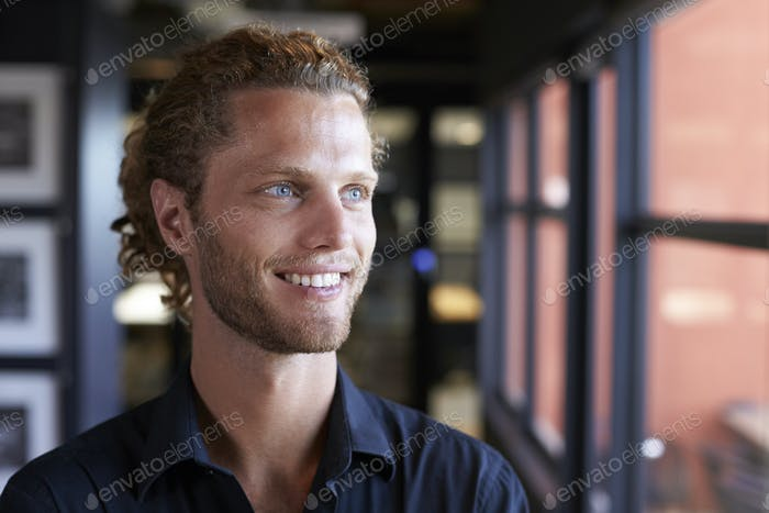 Millennial white male business creative smiling and looking out of the window in an office, close up