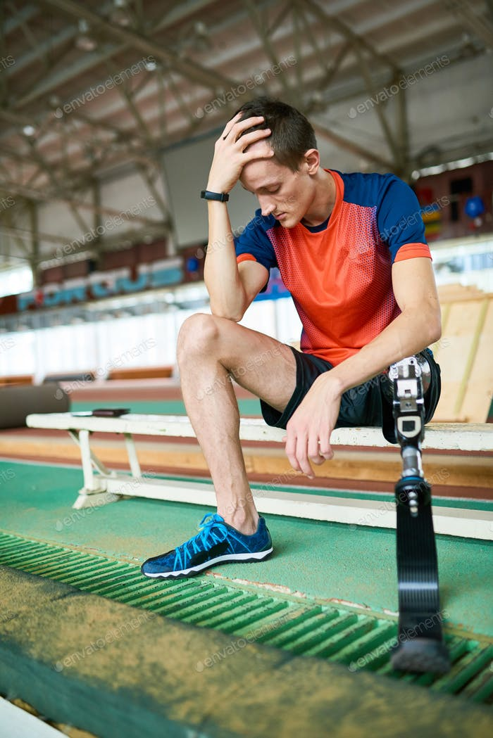 Handicapped Sportsman Sitting on Bench in Gym