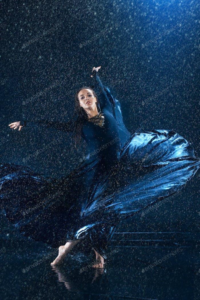 The young beautiful modern dancer dancing under water drops