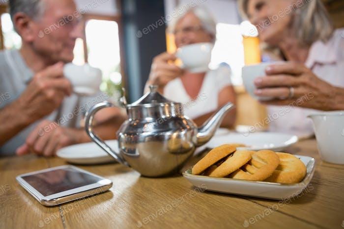Nahaufnahme von Teekanne, Handy und Kekse