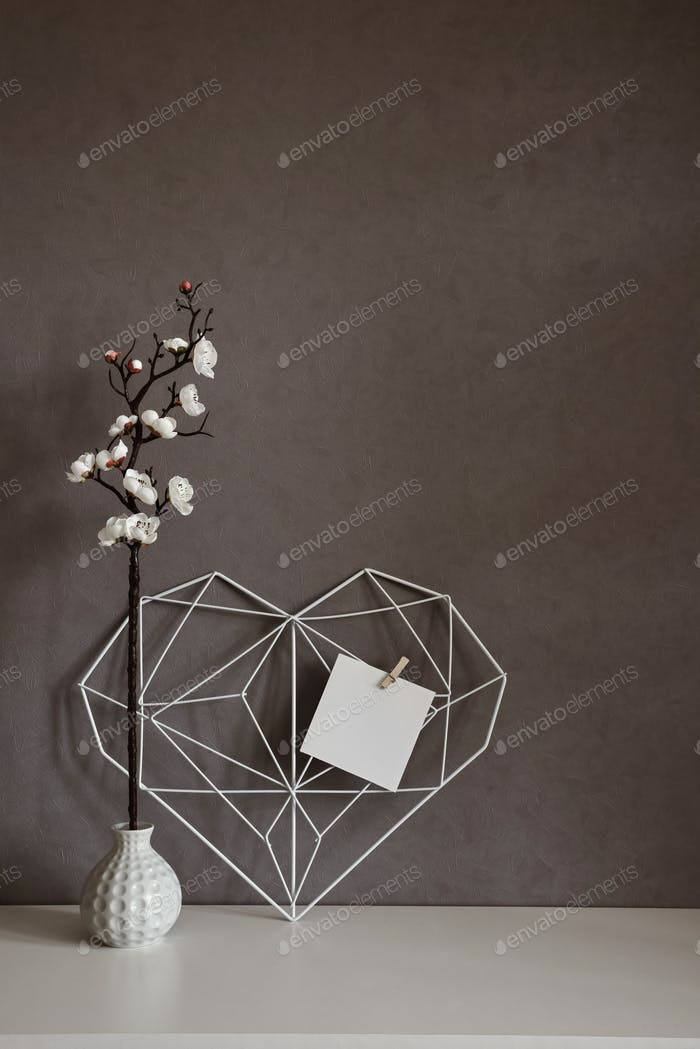 Elegant openwork heart with notes on concrete wall in the interior