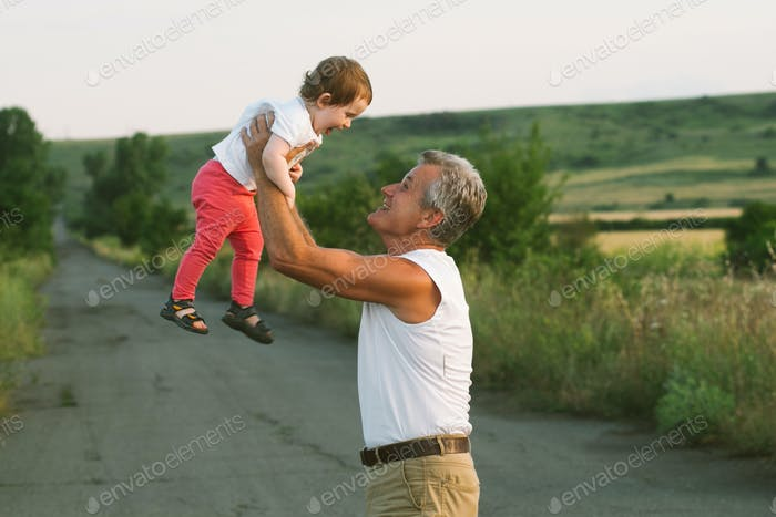 Grandfather with grandchild summer time together playing