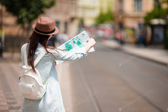 Youn girl with citymap walking on european streets. Travel caucasian woman with map outside during